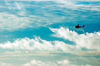 Seaplane flies across a cloudy sky, Maldives.