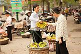 VIETNAM, Hanoi, a woman considers buying bananas from a street vendor