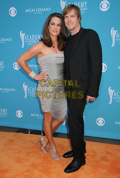 AMY & JACK INGRAM.45th Annual Academy Of Country Music Awards held at the MGM Grand Garden Arena, Las Vegas, NV, USA..April 18th, 2010.full length suit jacket grey gray strapless silver dress black hand on hip.CAP/ADM/BP.©Byron Purvis/AdMedia/Capital Pictures.