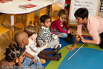 Education preschool 3-4 year olds circle time group of children holding up fingers to indicate number 3 female teacher leaning into to assist one girl horizontal