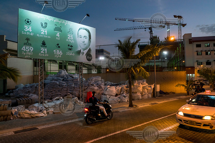 People pass a billboard showing the Maldivian President Abdulla Yameen and outlining what he has done for the country (34 football pitches, 21 watsan projects, 4 parks, 25 km of road, 459 hectares of land reclaimed, 21 harbor projects, 186 pharmacies and the Rasfannu artificial beach).