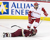 Matt Olinger 3 of the University of Wisconsin trips up Benn Ferriero 21 of Boston College. The Boston College Eagles defeated the University of Wisconsin Badgers 3-0 on Friday, October 27, 2006, at the Kohl Center in Madison, Wisconsin in their first meeting since the 2006 Frozen Four Final which Wisconsin won 2-1 to take the national championship.<br />