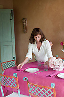 Maddalena Caruso applies the final touches to the table laid with a bright pink tablecloth and matching napkins