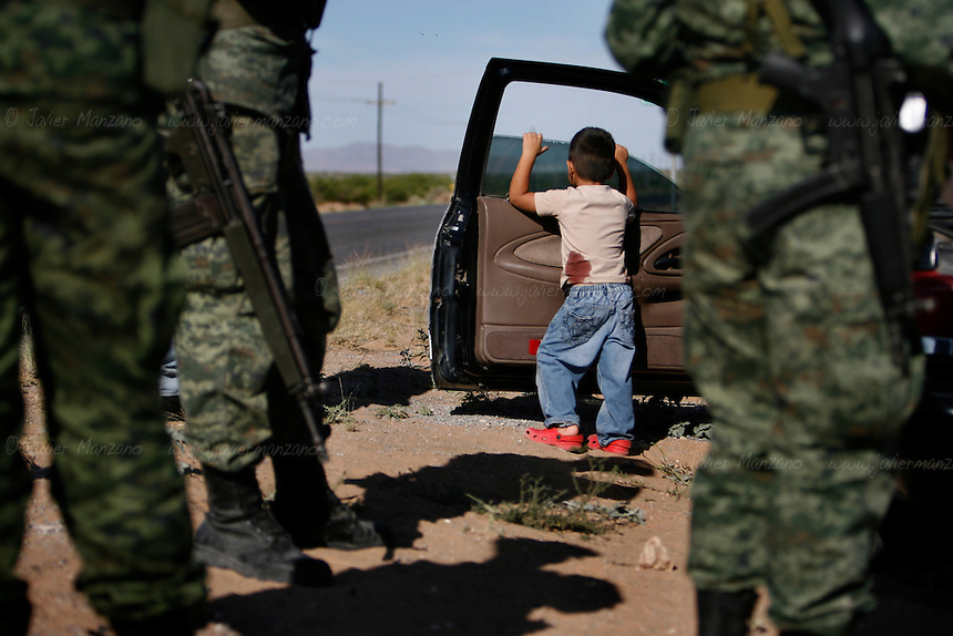 06/02/2010..A young boy stares off into the highway as soldiers stand guard next to the vehicle where the boy and his family were driving a few minutes earlier. As the family approached the City of Juarez, from a trip to the state of Sinaloa, a vehicle approached them on the 43rd Kilometer marker of the highway to Casas Grandes. They were signaled to stop the vehicle and pull over. As the family pulled over, armed men shot into the vehicle wounding the boy's father and mother. The father was taken by the armed men and forced into their vehicle which made a u-turn and drove back heading West.