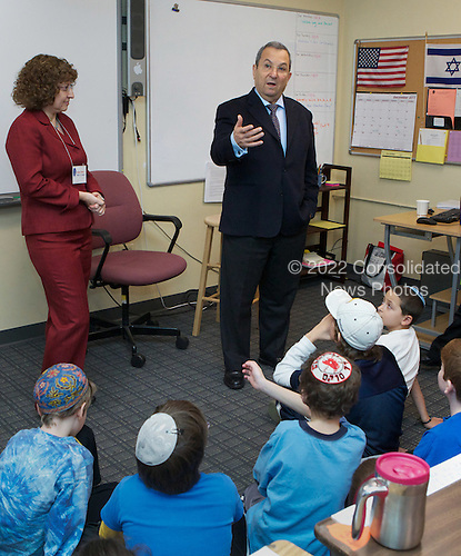 Israeli Defense Minister Ehud Barak speaks with students at the Jewish Primary Day School of the Nation's Capital in Washington DC, December 15, 2011 as Head of School Naomi Reem looks on.  Barak, also a former prime minister, toured the school, spoke in both Hebrew and English with kids in two classrooms and listened as they sang Israeli songs. The visit was part of the school's Yitzhak Rabin memorial series, named for the late prime minister.  ..Mandatory Credit: Chris Kleponis - H/O via CNP