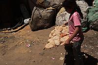 2011 Mokattam Garbage City (alla periferia del Cairo) il quartiere copto dove si vive in mezzo alla spazzatura raccolta: una bambina porta un vassoio di pane. Dietro di lei sacchi dell'immondizia.