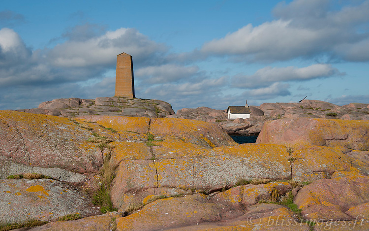 The hut at Segelskär Island is curiously framed by the blue sea and red granite rock in the outer archipelago near Tammisaari, Finland.