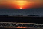 Foto: VidiPhoto<br /> <br /> DOMBURG – Een zeldzaam mooie zonsondergang woensdagavond in Domburg. Maar ook een onwerkelijke. Normaal gesproken zouden er op zo'n prachtige voorjaarsavond honderden mensen over het strand lopen om te genieten van de in zee zakkende zon. Echter, Domburg zit op slot. Voor toeristen en dagjesmensen is de kust verboden gebied en de politie houdt streng toezicht. Zeeland is de enige provincie in Nederland die al het recreatieverkeer heeft verboden. Zelfs bezitters van een tweede huisjes komen er niet in. Wat ze mislopen zijn de uitzonderlijk mooie zonsondergangen, dankzij een kraakheldere lucht zonder smog en vliegverkeer.