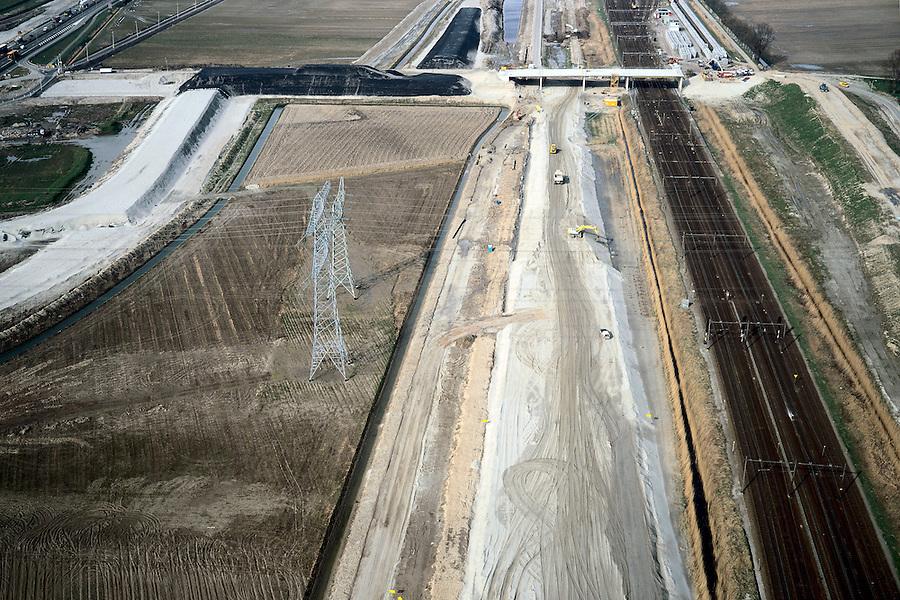 Nederland, Oude Moerdijkpolder, 08-03-2002;  in de richting van Station Lage Zwaluwe, direct links vh bestaande spoor (Rotterdam - Breda / Roosendaal) komt de HSL te lopen, aanleg aardebaan (zandlichaam onder constructie); aan de horizon Bredase Dijk: aanleg van viaduct (met landhoofden) waarmee de (nieuwe) sporen overgestoken zullen worden; zandlichamen nu bedekt met zwarte bitumen om verstuiving tegen te gaan; infrastructuur verkeer en vervoer spoor trein mobiliteit transport rangeerterrein wegenbouw landschap (zie ook Bredase dijk);<br /> luchtfoto (toeslag), aerial photo (additional fee)<br /> foto /photo Siebe Swart