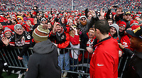Ohio State wide receiver Evan Spencer, defensive coordinator Luke Fickell and linebacker Darron Lee high five fans during the celebration for winning the national championship at Ohio Stadium on Jan. 24, 2015. More than 40,000 fans attended the celebration. (Adam Cairns / The Columbus Dispatch)