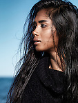 Young woman with long wet dark hair profile portrait at the beach with sea in the background