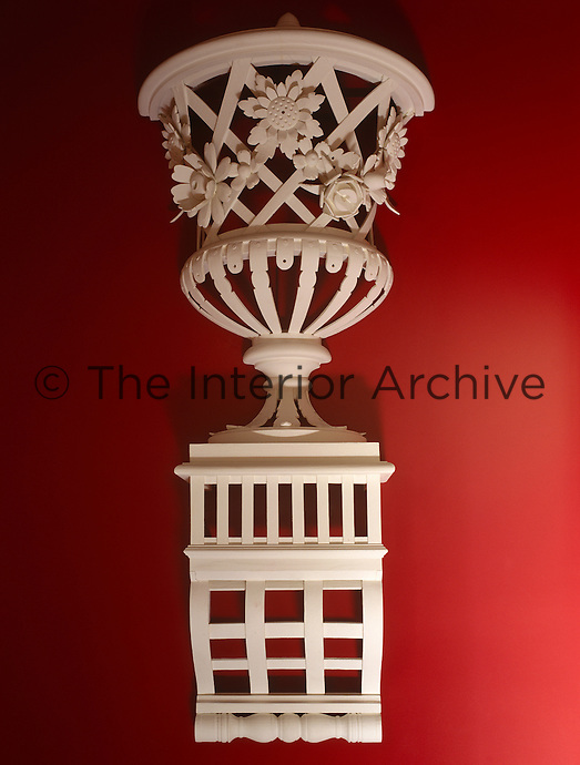 The red and white entrance hall is decorated with a sculptured urn on a plinth