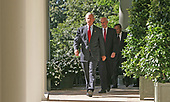 Washington, D.C. - September 3, 2005 -- United States President George W. Bush,  followed by Secretary of the United States Department of Homeland Security Michael Chertoff and United States Secretary of Defense Donald Rumsfeld walk down the colonade of the White House before President Bush's radio address on September 3, 2005. <br /> Credit: Dennis Brack - Pool via CNP