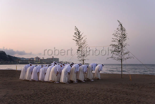Shrine priests and officials pray to the sea in a ritual known as hamaorisai at the start of the 3-day Reitaisai festival in Kamakura, Japan on  14 Sept. 2012.  Photographer: Robert Gilhooly