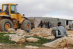 A Palestinian man sit during Israeli bulldozers demolish Palestinian homes in a disputed military zone in the area of Musafir Jenbah, which includes several villages, south of the West Bank town of Hebron on February 2, 2016. Israeli forces demolished at least a dozen buildings in a disputed military zone in the southern West Bank, leaving a number of families homeless, authorities and residents said. Israel has carried out a long campaign to relocate the residents of the area, which was declared a military zone by the Israeli government in the 1970s. Photo by Wisam Hashlamoun