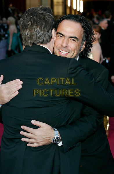 JAVIER BARDEM & ALEJANDRO GONZALEZ INARRITU.83rd Annual Academy Awards - Oscars.Kodak Theatre, Hollywood, CA, USA..February 27th, 2011 .half length back behind rear hug embrace gesture black white stubble facial hair tie .CAP/PE.©Peter Eden/Capital Pictures.