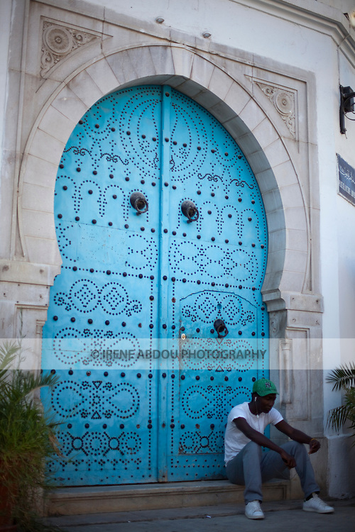 A man sits in front of a traditional Tunisian wood door in Tunis, Tunisia.