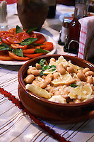 Salad with white beans in an earthenware bowl. Tomato and basil salad. White beans typical for south east Albania. Tradita traditional restaurant, Shkodra. Albania, Balkan, Europe.