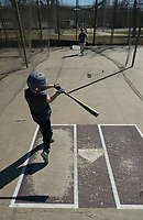 NWA Democrat-Gazette/ANDY SHUPE<br /> Colt Hood, 9, of Fayetteville swings Saturday, March 3, 2018, at a baseball as his father, Jeff Hood, works with him on his swing in the batting cages at Walker Park in Fayetteville. The Hoods were spending the day getting ready for Fayetteville Youth Baseball's tryouts next week.