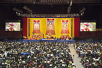 "Switzerland. Basel. St. Jakobshalle. The audience listens to His Holiness the Dalai Lama who is on stage during a public lecture on Bodhicitta. The topic of his talk is about Nagarjuna's Commentary on Bodhicitta which touches on two aspects of the awakening mind, the twin qualities of wisdom and compassion, which are necessary for anyone who aspires to be a better person and implement changes in their lives. The 14th and current Dalai Lama is Tenzin Gyatso, recognized since 1950. He is the current Dalai Lama, as well as the longest-lived incumbent, well known for his lifelong advocacy for Tibetans inside and outside Tibet. Dalai Lamas are amongst the head monks of the Gelug school, the newest of the schools of Tibetan Buddhism. The Dalai Lama, also called "" Ocean of Wisdom"" is considered as the incarnation of Chenresi, the Bodhisattva of compassion who is also the protective deity of Tibet. 7.02.2015 © 2015 Didier Ruef"