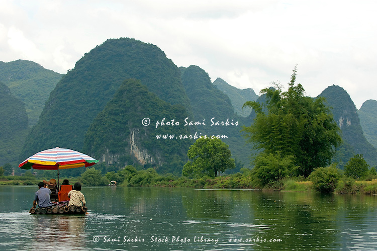 Chinese couple rowing a bamboo raft along the Yulong River with a European family on board, Yangshuo, Guangxi, China.