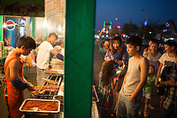 People purchase meat skewers at one of the many food stalls at Yangrenjie, or Meixin Foreigner Street, in northeastern Chongqing, China.