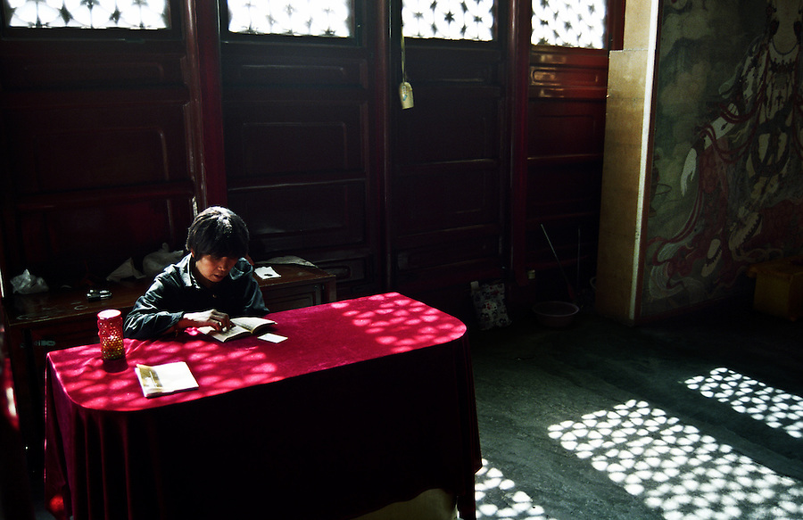 One of the attendants reading a book in the Lama Temple in Beijing, the most renowned Tibetan Buddhist temple outside Tibet.