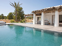 The house has a large terrace covered in a traditional manner with dried palm fronds that offer a shady space for relaxing and eating beside the pool