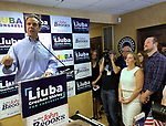 Massapequa, New York, USA. August 5, 2018. Governor ANDREW CUOMO speaks at podium, as (by cirucular wall sign) NY Senator JOHN BROOKS; LIUBA GRECHEN SHIRLEY, Congressional candidate for NY 2nd District; and her husband CHRIS SHIRLEY, at extreme right; and others listen at opening of joint campaign office, aiming for a Democratic Blue Wave in November midterm elections.