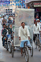 Indian man driving rickshaw with heavy load in street scene in city of Varanasi, Benares, Northern India