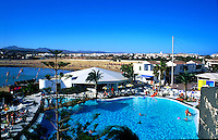 Swimming pool at resort in Calleta del Fuste, beach and hills in the background. Fuerteventura, Canary Islands, Spain