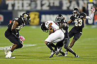 25 October 2011:  FIU defensive back Jose Cheeseborough (27), with linebacker Jordan Hunt (25) and defensive back Terrance Taylor (23) closing to assist, tackles Troy wide receiver Jaquon Robinson (83) in the third quarter as the FIU Golden Panthers defeated the Troy University Trojans, 23-20 in overtime, at FIU Stadium in Miami, Florida.