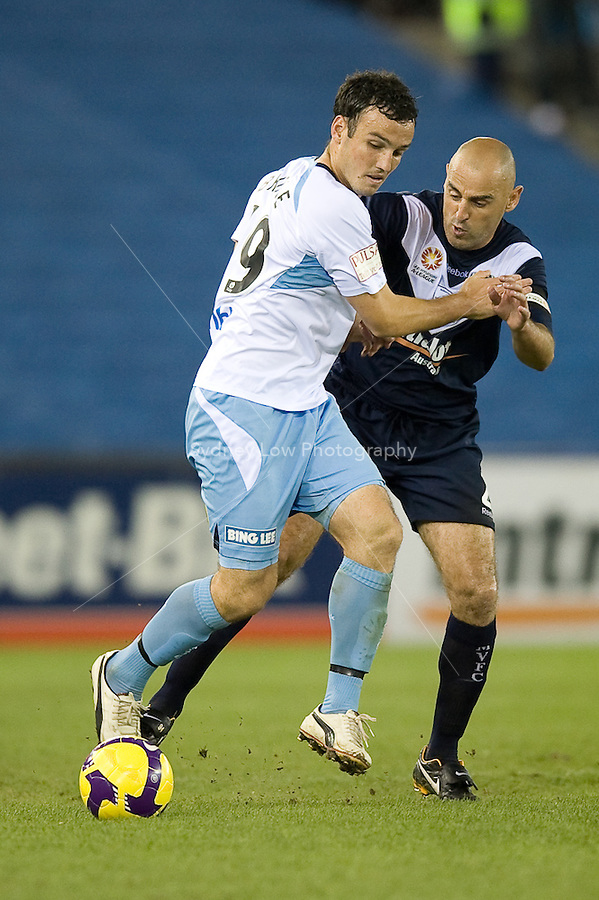MELBOURNE, AUSTRALIA - MARCH 20, 2010: Mark Bridge from Sydney FC fends off Kevin Muscat of Melbourne Victory in the final of the 2010 A-League between the Melbourne Victory and Sydney FC at Etihad Stadium on March 20, 2010 in Melbourne, Australia. Photo Sydney Low www.syd-low.com