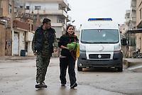 Sehid Xebat Hospital unter YPG-Verwaltung in Qamishli, Rojava/Syrien.<br /> Im Bild: Einer Kaempferin der YPJ (rechts im Bild), der Fraueneinheit in der Armee der YPG, wurde in Kobane der linke Arm zerschossen. Ein Operateur hat mit externer Fixierung die zertruemmerten Knochen stabilisiert. Sie wird von einem Krankenhausmitarbeiter und YPG-Kaempfer begleitet (links).<br /> 14.12.2014, Qamishli/Rojava/Syrien<br /> Copyright: Christian-Ditsch.de<br /> [Inhaltsveraendernde Manipulation des Fotos nur nach ausdruecklicher Genehmigung des Fotografen. Vereinbarungen ueber Abtretung von Persoenlichkeitsrechten/Model Release der abgebildeten Person/Personen liegen nicht vor. NO MODEL RELEASE! Nur fuer Redaktionelle Zwecke. Don't publish without copyright Christian-Ditsch.de, Veroeffentlichung nur mit Fotografennennung, sowie gegen Honorar, MwSt. und Beleg. Konto: I N G - D i B a, IBAN DE58500105175400192269, BIC INGDDEFFXXX, Kontakt: post@christian-ditsch.de<br /> Bei der Bearbeitung der Dateiinformationen darf die Urheberkennzeichnung in den EXIF- und  IPTC-Daten nicht entfernt werden, diese sind in digitalen Medien nach §95c UrhG rechtlich geschuetzt. Der Urhebervermerk wird gemaess §13 UrhG verlangt.]