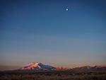 Winter sunrise, Winnemucca Mountain, snow, and the moon from the the Winnemucca Dunes along US-95 north of town.
