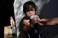 leaving0627 Alondra Rosario, 21 months, holds her Arizona ID card. She is a U.S. citizen and her family got her the id card before moving to PA.  (Pat Shannahan/ The Arizona Republic)