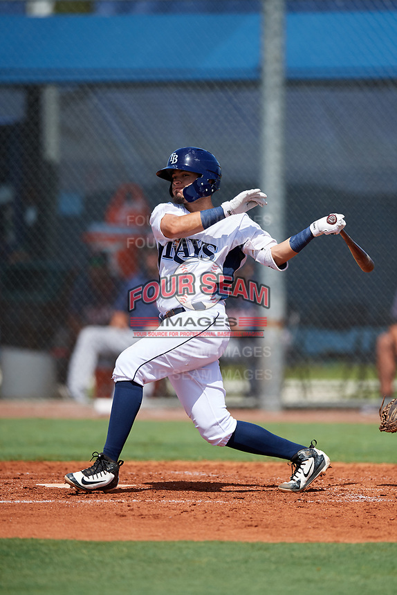 GCL Rays second baseman Cristhian Pedroza (19) follows through on a swing during a game against the GCL Twins on August 9, 2018 at Charlotte Sports Park in Port Charlotte, Florida.  GCL Twins defeated GCL Rays 5-2.  (Mike Janes/Four Seam Images)