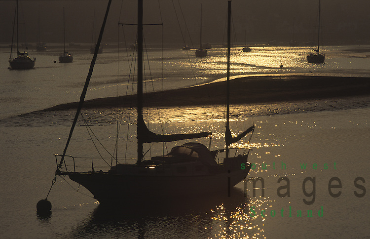 Sunrise on the River Urr yachts silhouetted against the sun looking across river to Kippford on the Solway Firth coast from Glen Isle Galloway Scotland UK