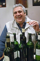 Jean-Louis Poudou with lots of bottles. Domaine La Tour Boisee. In Laure-Minervois. Minervois. Languedoc. Owner winemaker. Tasting wine. France. Europe. Bottle.