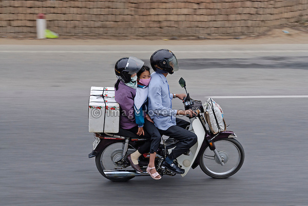 Asia, Vietnam, near Hue. Vietnamese family with child and baggage on motorbike.