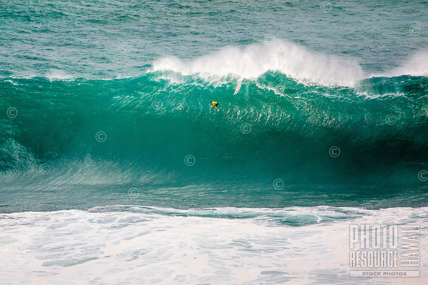 """Surfer Grant """"Twiggy"""" Baker free falling from the top of a wave at the 2016 Big Wave Eddie Aikau Contest, Waimea Bay, North Shore, O'ahu."""