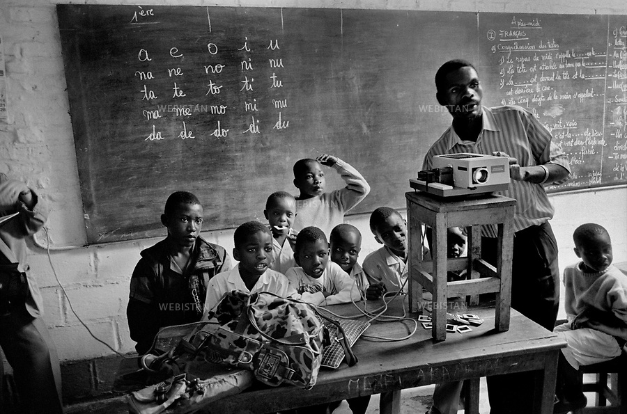 1995. Zaire. Democratic Republic of the Congo (DRC). Sud-Kivu Province. Bukavu. A teacher projects slides to a class of children at the Heri-Kwetu Centre which has for mission to help mentally handicapped children, children with motor disability, children suffering from deafness, muteness or blindness. Zaïre. République Démocratique du Congo (RDC). Province du Sud-Kivu. Bukavu. Un instituteur projette des diapositives à une classe d'enfants du Centre Heri-Kwetu qui a pour mission d'aider les enfants handicapés mentaux et moteurs, les sourds et muets, et les aveugles.