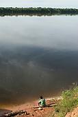 Xingu Indigenous Park, Mato Grosso State, Brazil. Aldeia Tuba Tuba (Yudja). A boy prepares a fishing line.