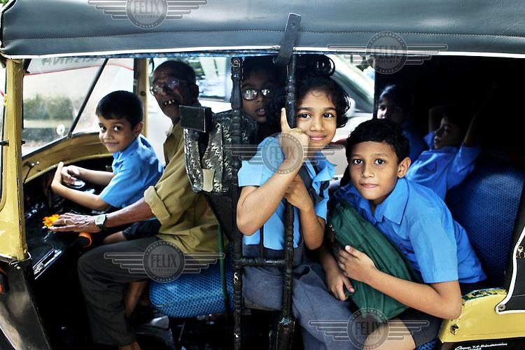 School children travel home from school by autorickshaw.