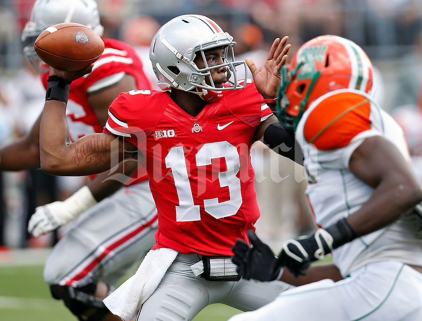 Ohio State Buckeyes quarterback Kenny Guiton (13) steps up in the pocket to throw the ball to one of his receivers against Florida A&M Rattlersin the 2nd quarter during their college football game at Ohio Stadium on September 21, 2013.  (Dispatch photo by Kyle Robertson)