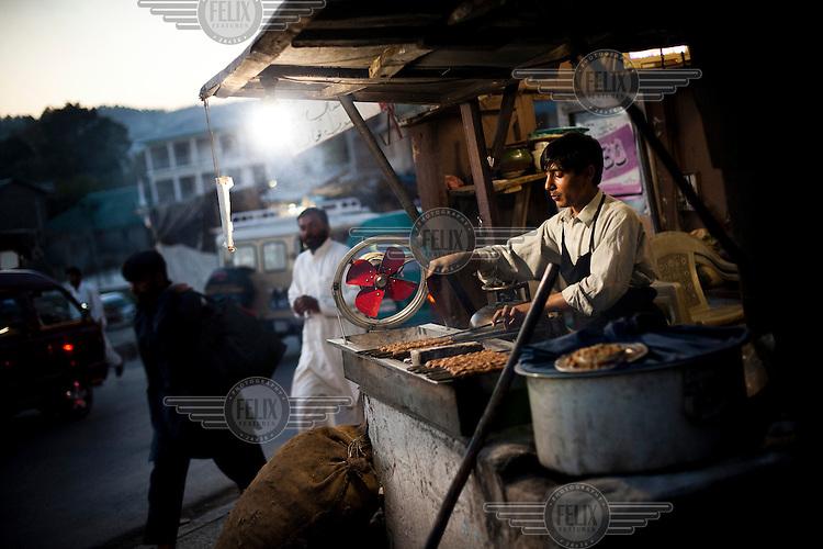 A roadside cook prepares kebabs.