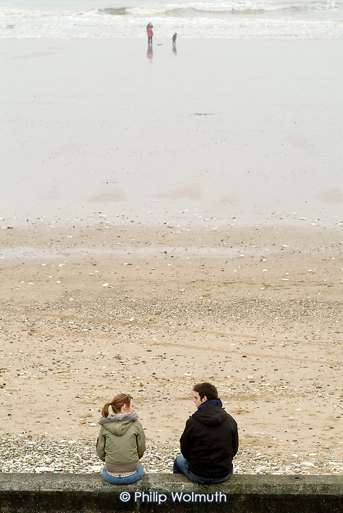A young couple sit on the sea wall in the Yorkshire seaside resort of Bridlington on Easter Bank Holiday.