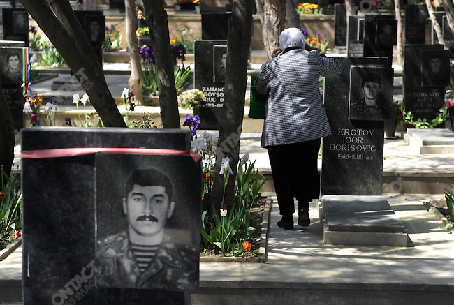 In Martyrs' Lane a woman walked past graves of Azeri soldiers killed in the conflict in Nagorno-Karbakh in the early 1990s. Baku, Azerbaijan, May 13, 2011.