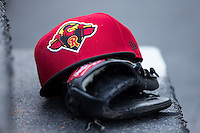 A Rochester Red Wings hat sits on top of a glove in the visitors dugout during the game against the Charlotte Knights at BB&T BallPark on August 8, 2015 in Charlotte, North Carolina.  The Red Wings defeated the Knights 3-0.  (Brian Westerholt/Four Seam Images)