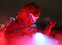 July 18, 2014, Tokyo, Japan - A visitor looks closely at a 6.6 meter tall replica model of Godzilla at Tokyo Midtown in downtown Tokyo on Friday, July 18, 2014. The Godzilla display runs from July 18 to August 31. (Photo by AFLO)